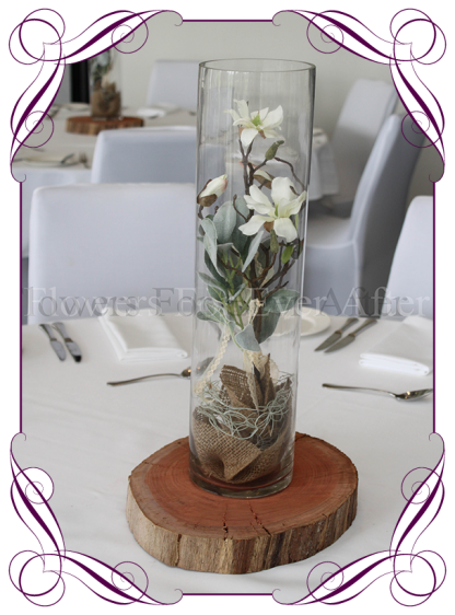 Rustic table centerpiece for hire in Melbourne and surrounds. Magnolia and burlap in a cylinder vase on a wooden base.