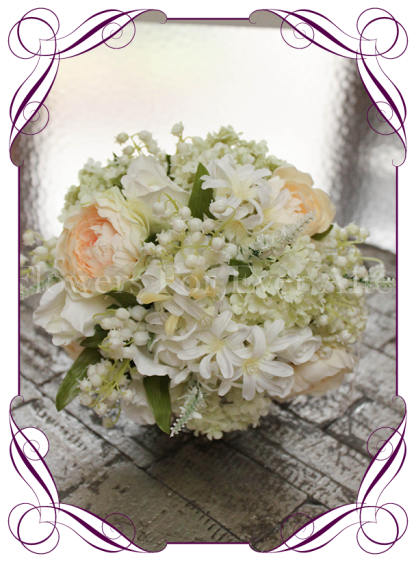 Pretty feminine bridal bouquet featuring lily of the valley, white roses, ranunculus, peach roses, snowball, hyacinth and foliages. A beautiful semi structured vintage / boho look