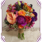 Vibrant colourful silk artificial wedding bouquet. A posy of mixed textures and blooms in a colorful mix. With ranunculi, roses, thistle, berries, baby's breath, in pink, coral, orange, red, purple and magenta colours.