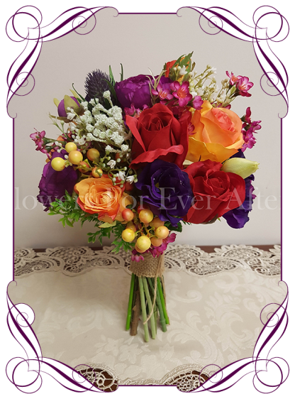 Vibrant colourful silk artificial wedding bouquet. A Bridesmaids posy of mixed textures and blooms in a colorful mix. With ranunculi, roses, thistle, berries, baby's breath, in pink, coral, orange, red, purple and magenta colours.