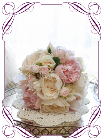 An elegant and romantic silk artificial bridesmaids wedding flower bouquet with pastel colours in blush, pink, off white / ivory. With peonies, roses, protea buds and orchids. Classic and sweet. Shipping world wide. Buy online