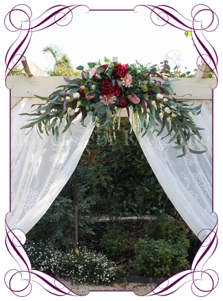 Silk artificial burgundy and dusty pink wedding arbor arch garland decoration. With protea, peonies, dahlia, native Australian gum leaves in a rustic design. Buy online. Shipping worldwide.