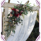 Silk artificial burgundy and dusty pink wedding arbor arch garland decoration. With protea, peonies, dahlia, native Australian gum leaves in a rustic corner design. Buy online. Shipping worldwide.
