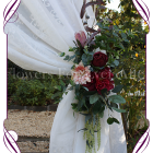 Silk artificial burgundy and dusty pink wedding arbor arch tie back decoration. With protea, peonies, dahlia, native Australian gum leaves in a rustic design. Buy online. Shipping worldwide.